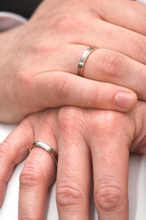pareja de esposos: Dos manos de una pareja casada con anillos de boda Foto de archivo