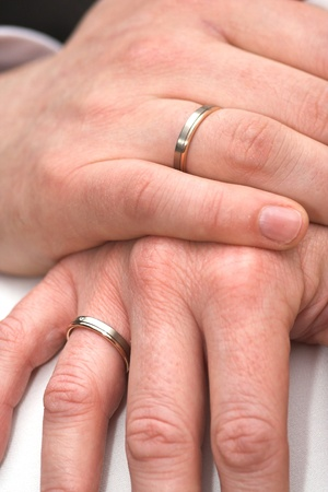 Two hands of a married couple with wedding rings