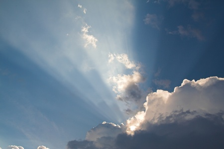 Blue sky with sunrays breaking through a cloud Stock Photo