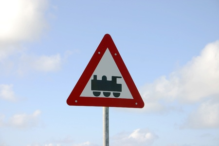 Sign that shows railroad crossing in front of a blue sky photo