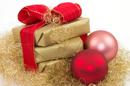 Three golden gifts and two Christmas balls with a white background Stock Photo