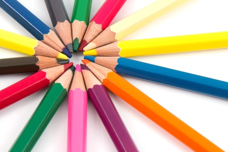 Different colored pencils in a circled array with a white background photo