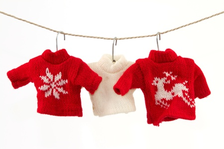 knitted: Three pullovers and a clothesline with a white background