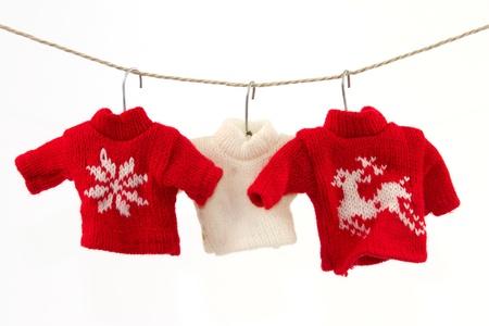 maglioni: Tre pullover e una clothesline con uno sfondo bianco