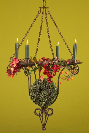 Burning candlestick with fall decoration and a green background Stock Photo