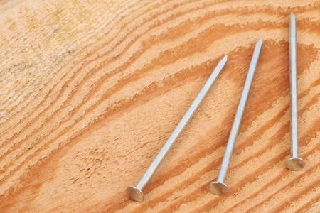 structured: Tres clavos sobre un fondo de madera estructurada
