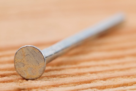 Closeup of a nail on a structured wooden background photo