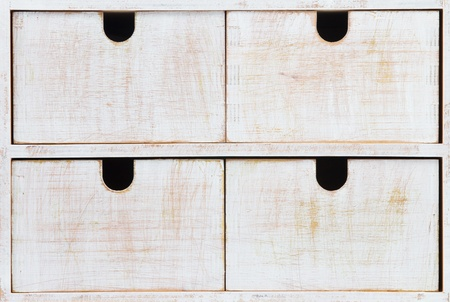 Four white wooden drawers with black holes Standard-Bild