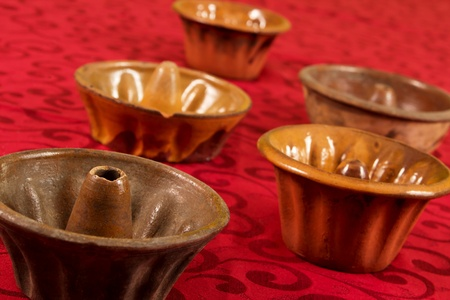 ornated: Five brown bowls on a red ornated background Stock Photo