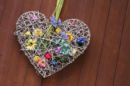 Deko-Herz mit Blumen und einem hölzernen Hintergrund Standard-Bild - 11323528