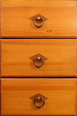 Three wooden drawers with metal grips