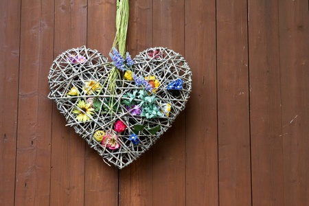 Deko-Herz mit Blumen und einem hölzernen Hintergrund Standard-Bild - 11323579