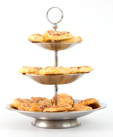 Silver etagere with pizza snacks in front of a white background