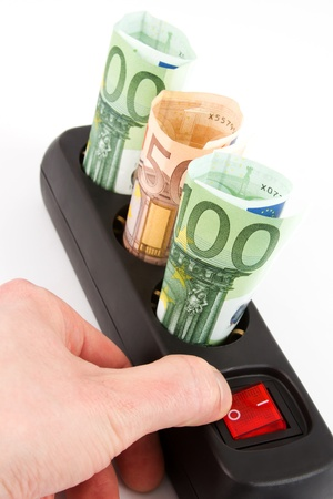 electricity tariff: Three Euro banknotes in a black plugbar and a hand on the switch in front of a white background Stock Photo