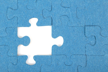 Missing blue piece of a puzzle in front of a white background Stock Photo