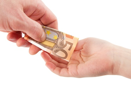 Hand giving a banknote in a hand of a child isolated on a white background photo