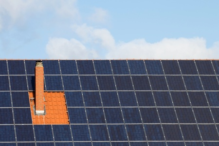 monocrystalline: Many solar panels around a chimney on a roof