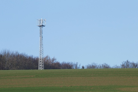 Cell tower in nature in front of a blue sky photo