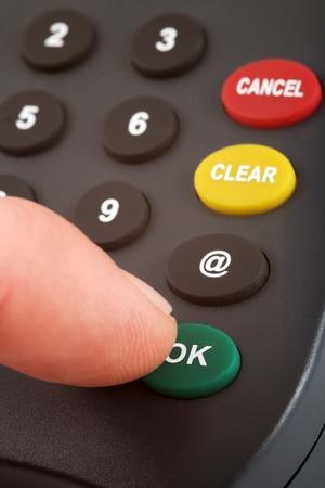 teclado numerico: Teclado numérico con un dedo presionando un botón verde Foto de archivo