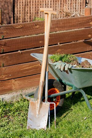 Full barrow with gloves a spade and a garden fork in front of a compost photo