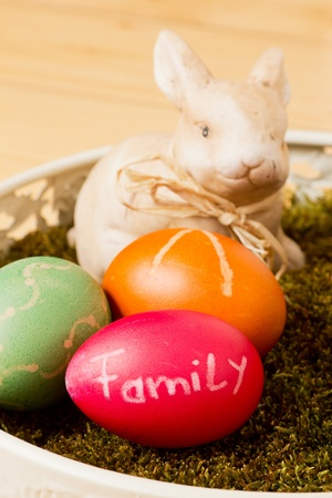Easter basket with moss colorful eggs and a bunny in front of a wooden background Stock Photo - 13165663