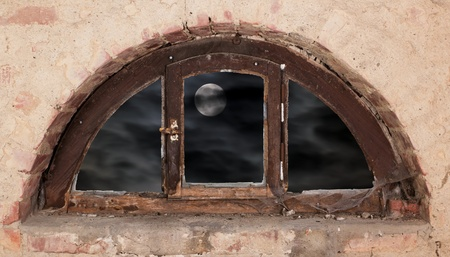 semicircular: Old semicircular wooden window in front of a dark sky with full moon