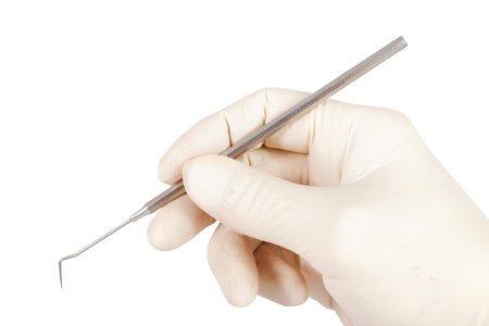 Hand with sterile glove holding a dental probe over a white background