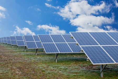 Field with many solar cells in front of a blue sky with clouds photo
