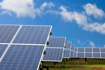 Field with many solar cells in front of a blue sky with clouds Stock Photo