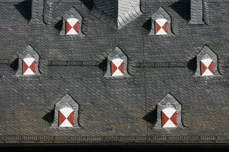 top seven: Dark roof of a historical building with seven symmetric dormers Stock Photo