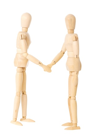 Two wooden dolls doing a handshake over a white background photo