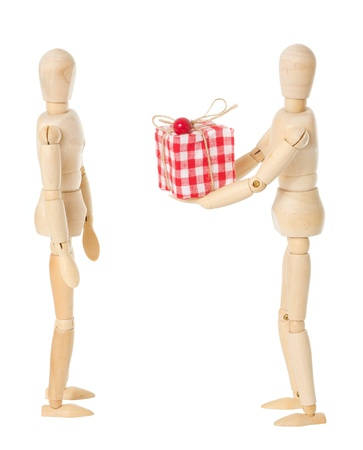 A wooden doll gives a red present to another wooden doll over a white background Stock Photo - 13651478