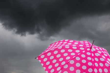 A pink umbrella in front of dark rain clouds