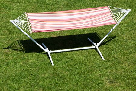 Colorful hammock in the sun standing on the green grass in the garden