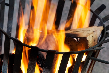 Closeup of an old rusty fire basket with burning wood Stock Photo