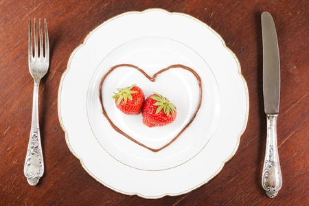 White plate with two strawberries in a chocolate heart and a fork and a knife on a wooden table photo