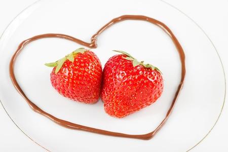 Closeup von zwei Erdbeeren in einer Schokolade Herz auf einem weißen Teller Standard-Bild - 14192231