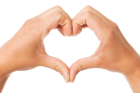 Two hands of a woman forming a heart shape over a white background photo