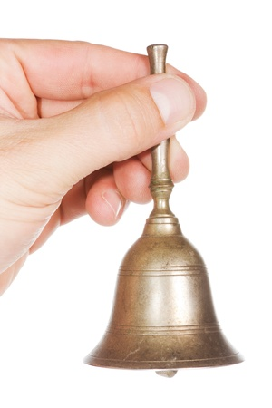 to chime: Hand with an old golden bell over a white background