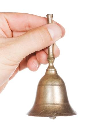 campanas: Mano con una vieja campana de oro sobre un fondo blanco