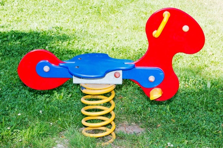 Colorful play equipment in the grass on a playground photo