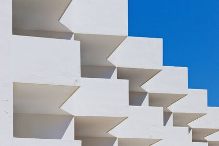 Detail of a white building in front of a blue sky photo