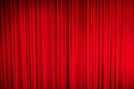Red closed curtain with light spots in a theatre