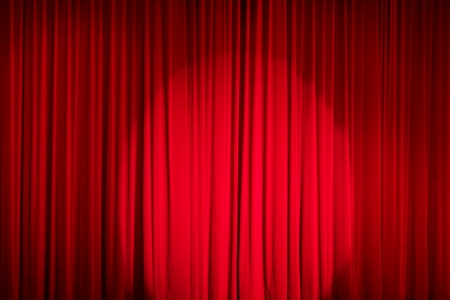 Red closed curtain with a light spot in a theatre