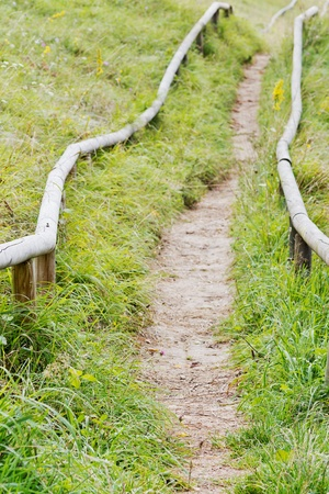 hand rail: Hiking path in the meadow with a wooden hand rail Stock Photo