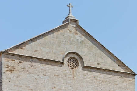 Detail of a church with a stone cross in front of a blue sky Standard-Bild
