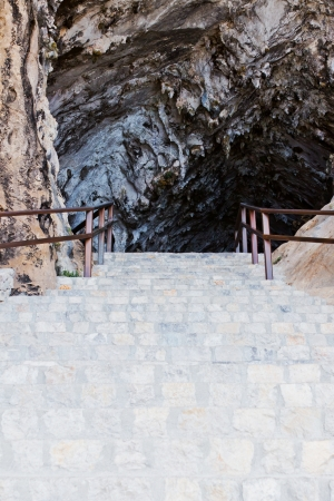Entrance of a dripstone cave with stairs Standard-Bild