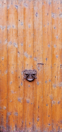 Closeup of a weathered wooden door with a rusty knocker