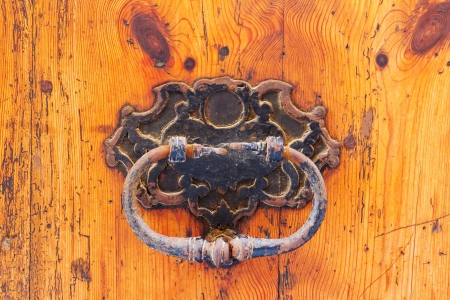 Closeup of a rusty old knocker of a weathered wooden door