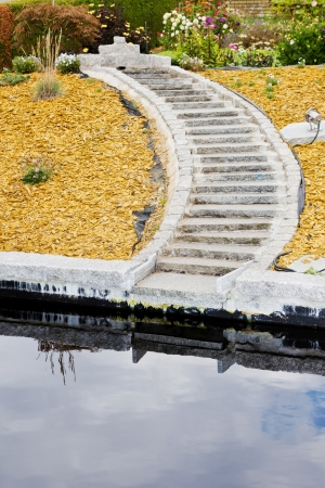 Detail of curved stairs in a new arranged garden with a pond